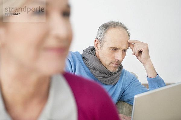 Nahaufnahme einer Frau mit einem Mann, der im Hintergrund an einem Laptop arbeitet.