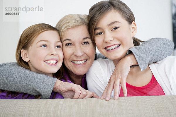 Porträt einer Frau, die mit ihren Enkelinnen lächelt