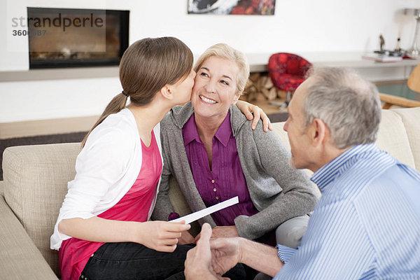 Mädchen, das ihre Großmutter küsst, während ihr Großvater neben ihnen sitzt.