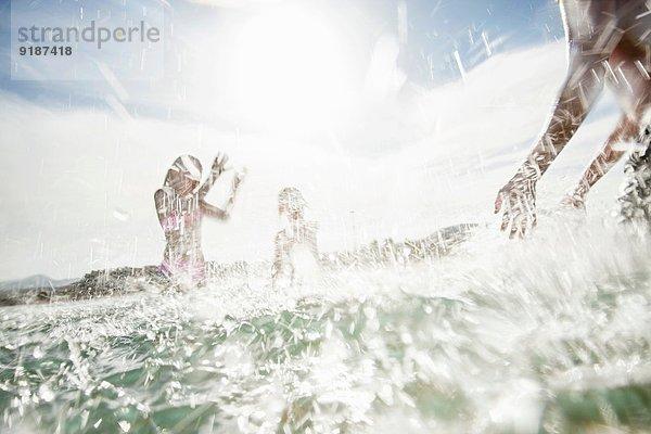 Vater mit Sohn und Tochter, die sich am Strand bespritzen.