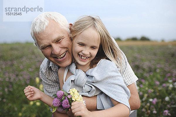 Porträt eines glücklichen Grossvaters und einer glücklichen Enkelin mit gepflückten Blumen auf einer Wiese
