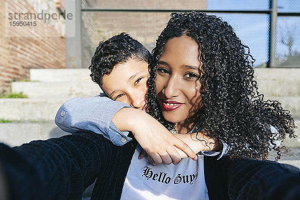 Porträt einer glücklichen Mutter und eines glücklichen Sohnes, die zusammen auf Stufen sitzen, die sich selbst machen