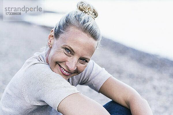 Glückliche Frau am Flussufer sitzend