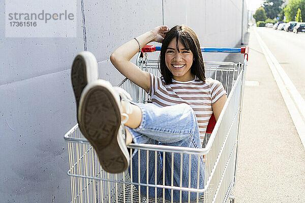 Glückliche Frau sitzt im Einkaufswagen