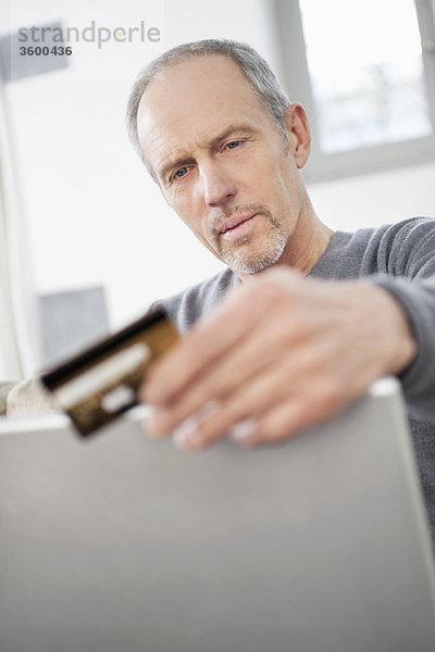 Mann beim Online-Shopping mit einem Laptop