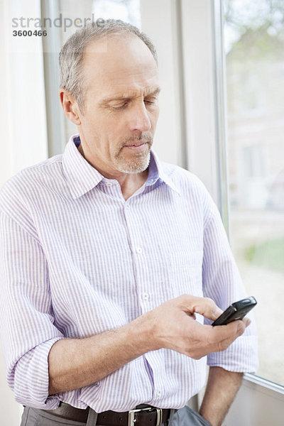 Nahaufnahme eines Mannes Textnachrichten auf einem Mobiltelefon