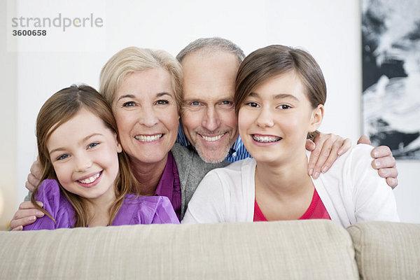 Ein Paar lächelt mit seinen Enkelinnen.