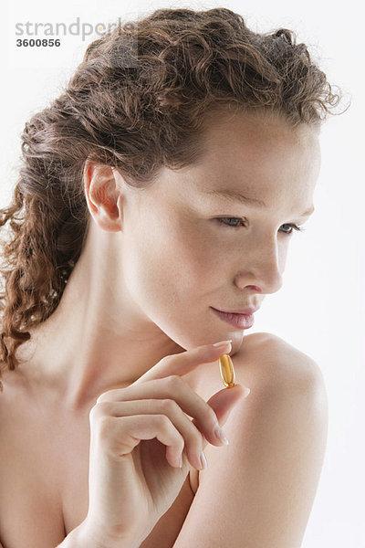 Nahaufnahme einer Frau mit einer Dorschleberölkapsel