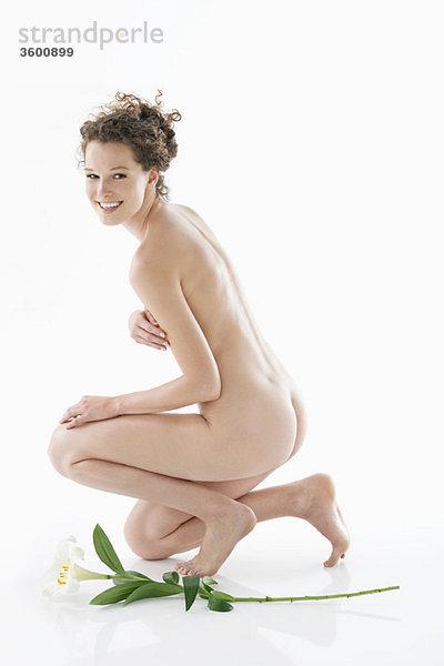 Nackte Frau kniend neben einer Blume und lächelnd