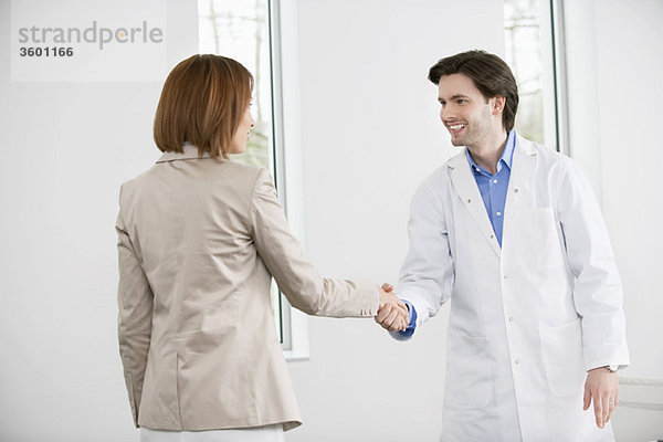 Arzt schüttelt die Hand mit einer Frau