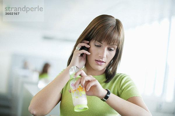 Geschäftsfrau im Gespräch mit dem Handy und Überprüfung der Uhrzeit