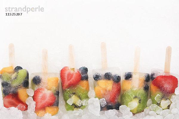 Reihe von sechs Fruchteis-Lollies mit frischen Früchten auf weißem Grund