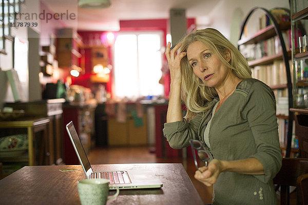Reife Frau schaut abgelenkt weg, während sie den Laptop zu Hause benutzt.