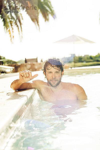 Mann entspannt im Pool, Portrait