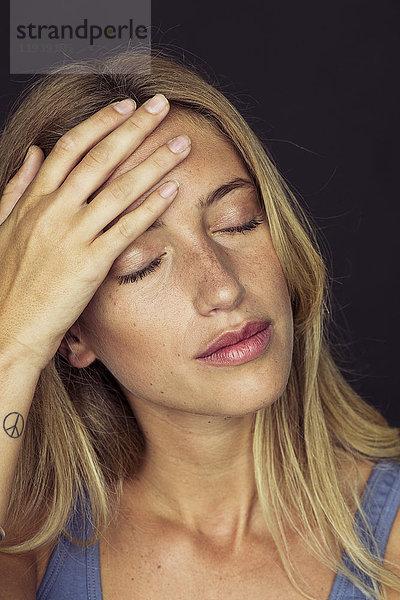 Junge Frau berührt ihre Stirn mit geschlossenen Augen