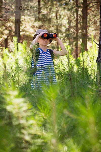 Junge mit Fernglas im Wald