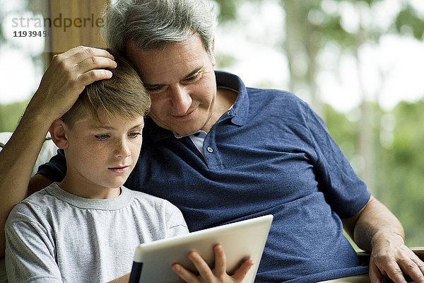 Mann mit Kind mit digitalem Tablett