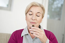 Nahaufnahme einer Frau, die Aromatherapieöl riecht