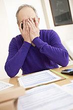 Mann sieht besorgt aus, während er sein Steuerformular ausfüllt.