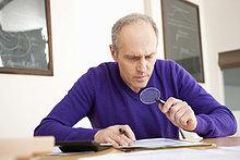 Mann, der durch eine Lupe schaut, während er sein Steuerformular ausfüllt.