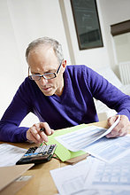 Mann mit Taschenrechner und Ausfüllen des Steuerformulars