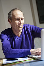 Mann arbeitet an einem Laptop
