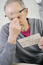Mann, der beim Lesen einer Postkarte ernsthaft aussieht