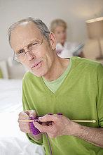 Porträt eines strickenden Mannes mit einer Frau im Hintergrund