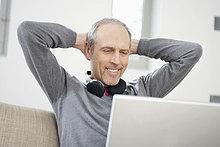 Mann schaut auf einen Laptop und lächelt