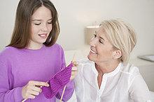 Frau bringt ihrer Enkelin das Stricken bei