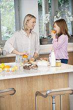 Frau macht Orangensaft mit ihrer Tochter in der Küche