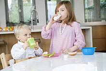 Mädchen trinkt Milch mit ihrem Bruder am Frühstückstisch.