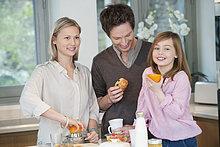 Familie bereitet Frühstück in der Küche zu