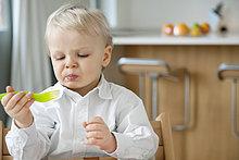 Junge, der mit einer Gabel isst und ein Gesicht macht.