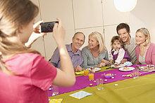 Mädchen beim Fotografieren ihrer Familie mit einem Fotohandy