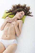 Frau bedeckt ihre Brüste und lächelt.