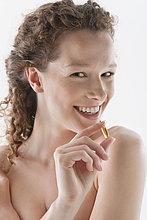 Porträt einer Frau, die eine Dorschleberölkapsel hält und lächelt