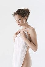 Nackte Frau, die sich mit einem Sarong bedeckt.