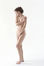 Nackte Frau, die die Leiste mit der Hand bedeckt.