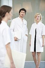 Männlicher Arzt stehend mit zwei Ärztinnen