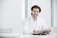 Männlicher Arzt mit ärztlichem Befund und Lächeln