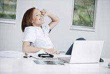 Ärztin im Büro sitzend und lächelnd