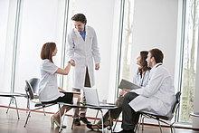 Arzt schüttelt sich die Hand mit einer Ärztin.