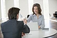 Geschäftsfrau, die einem Geschäftsmann eine Kreditkarte gibt