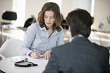 Frau schreibt ein Dokument mit einem Mann, der vor ihr sitzt.