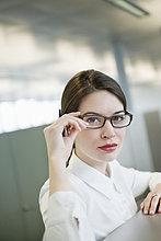 Porträt einer Geschäftsfrau, die ihre Brille anpasst