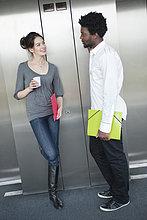 Geschäftsfrau hält einen Einwegbecher und spricht mit ihrem Kollegen