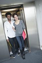 Geschäftsfrau, die mit ihrer Kollegin aus dem Aufzug kommt.