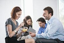 Frau isst Essen mit ihren Kollegen, die mit ihr sitzen