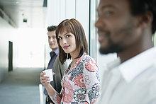 Geschäftsfrau mit einem Einwegbecher zwischen ihren Kollegen